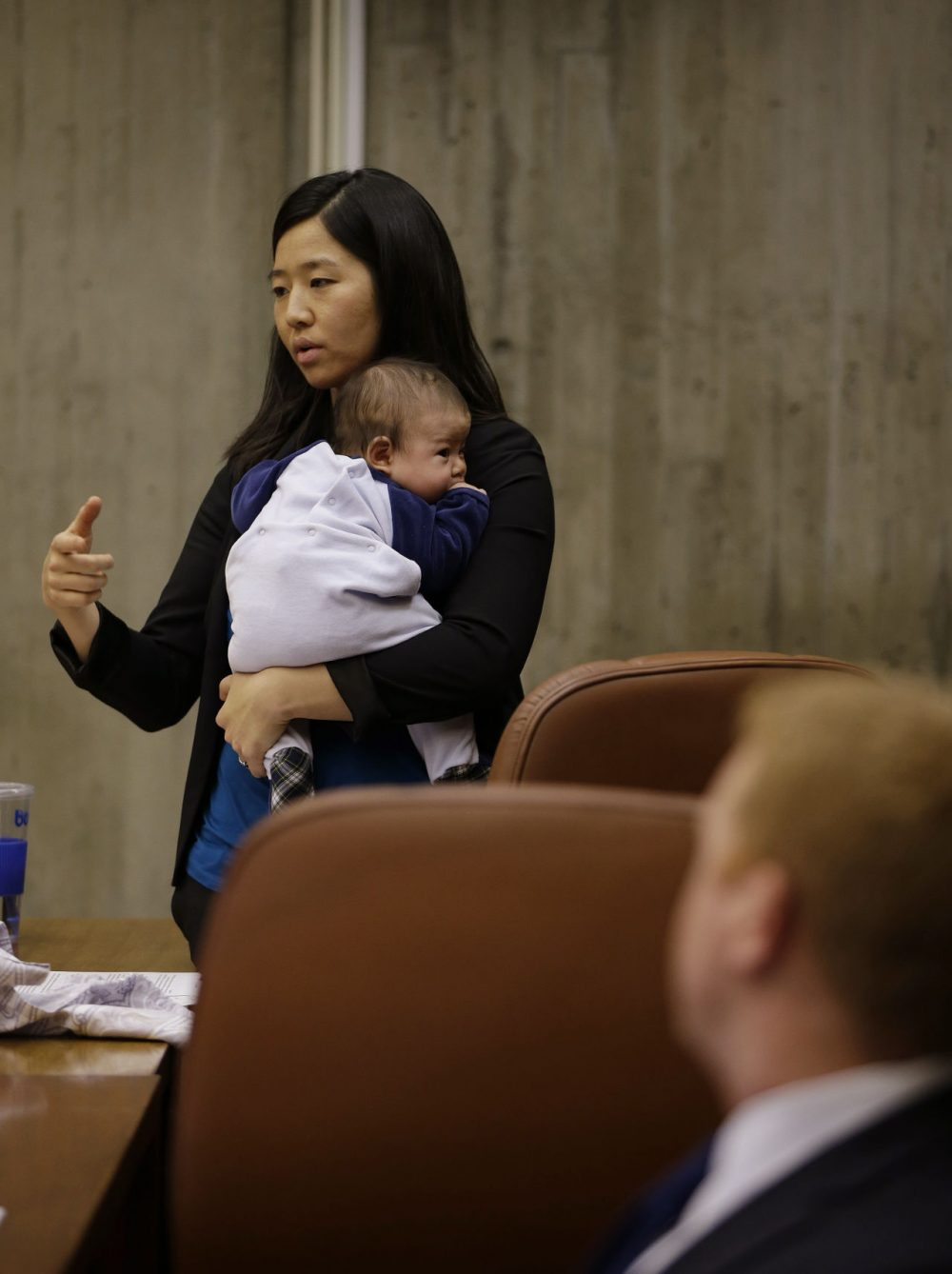 Boston City Councilwoman Michelle Wu holds her 11 week-old son as she asks a question of a member of Boston 2024. (Stephan Savoia/AP)