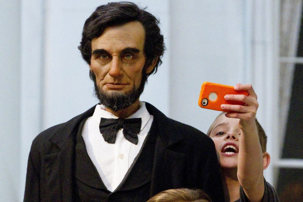 Zachary Hollis, 11, of Breadstown, Ill., stretches to capture a selfie with a life-size figure of Abraham Lincoln at the Abraham Lincoln Presidential Museum in Springfield, Ill. (Randy Squires/AP)