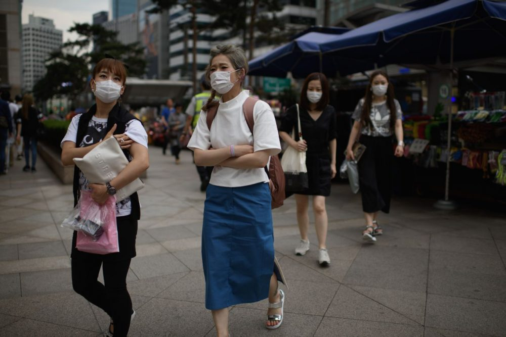 Women wearing face masks walk on a street in Seoul on June 5, 2015. South Korea reported a fourth death from Middle East Respiratory Syndrome (MERS), as an infected doctor fueled fears of a fresh surge in cases and prompted Seoul's mayor to declare 'war' on the virus. (Ed Jones/AFP/Getty Images)
