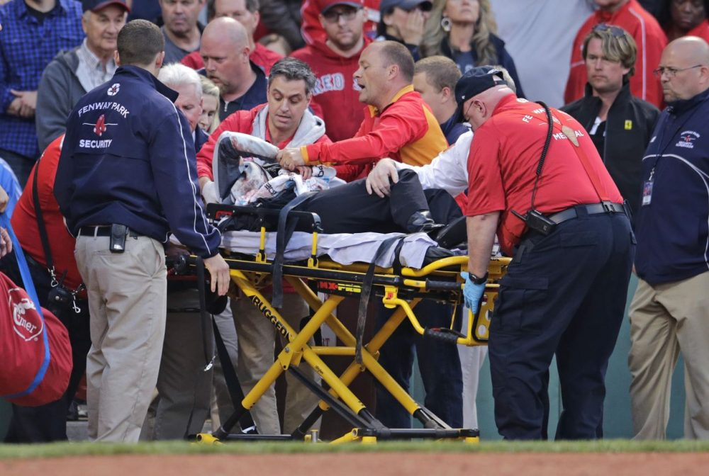 Tonya Carpenter, who was accidentally hit in the head with a broken bat by Oakland Athletics' Brett Lawrie, is helped from the stands during a game against the Red Sox at Fenway Friday. (Charles Krupa/AP)