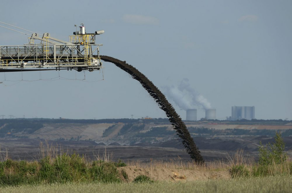 A conveyor bridge deposits soil removed from one end of the Welzow Sued open-pit lignite coal mine to allow excavators to reach the coal underneath as the Schwarze Pumpe coal-fired power plant stands behind on May 28, 2015 near Welzow, Germany. (Sean Gallup/Getty Images)