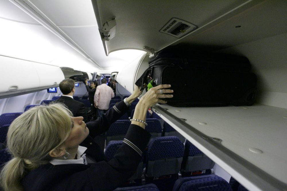 American Airlines flight attendant Renee Schexnaildre demonstrates the overhead baggage area during a media preview of the airline's new Boeing 737-800 jets, at Dallas Fort Worth International Airport in Grapevine, Texas. (Donna McWilliam/AP)
