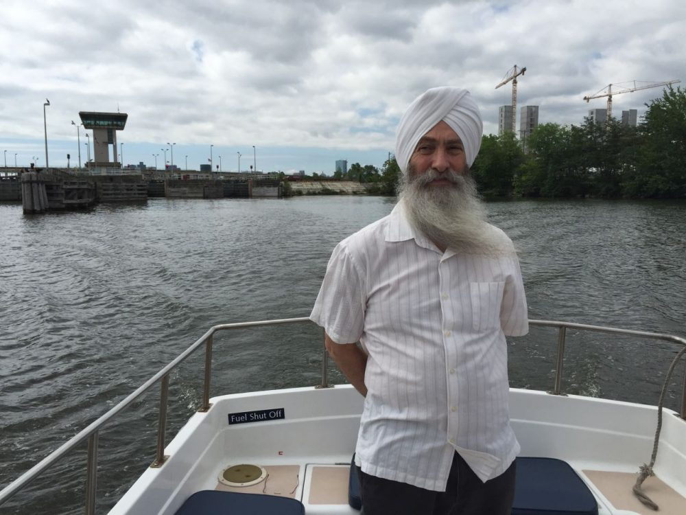 EkOngKar Singh Khalsa, executive director of the Mystic River Watershed Association, aboard a Boston Harbor Cruises water taxi on the freshwater side of the Mystic River. The Amelia Earhart Dam and Assembly Row construction is in the distance. (Anthony Brooks/WBUR)