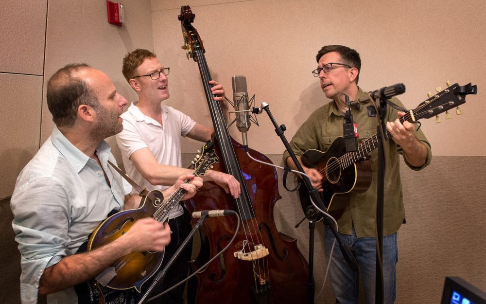 The Lonesome Trio performs in the Here & Now studios. From left: Jacob Tilove on mandolin, Ian Riggs on bass and Ed Helms on guitar. (Robin Lubbock/WBUR)