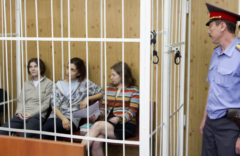 Yekaterina Samutsevich, Nadezhda Tolokonnikova, Maria Alekhina, members of feminist punk group Pussy Riot sit behind bars at a court room in Moscow in 2012. (Misha Japaridze/AP)