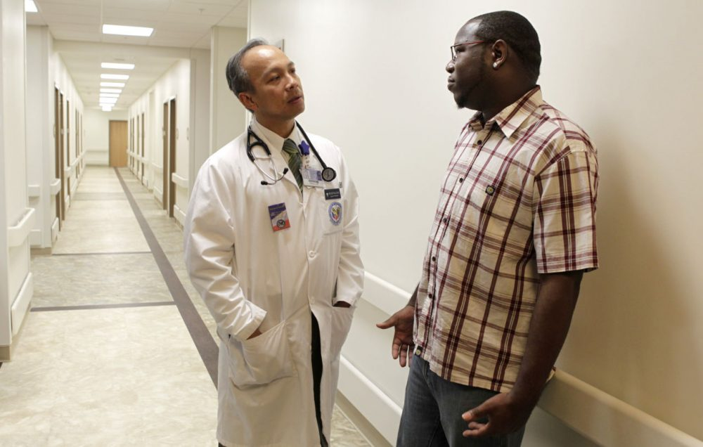 Dr. Dzung Le, D.O. talks with retired Air Force Staff Sgt. Shalum Scott in the hallway after his appointment at the Department of Veteran's Affairs Clinic in Fort Worth, Texas in 2010. (Sharon Ellman/AP)