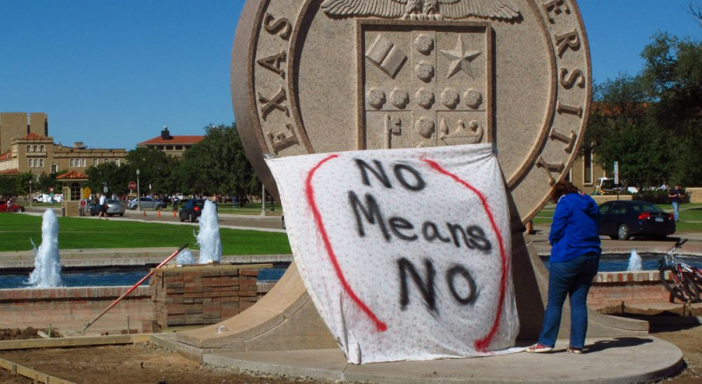 "Harvey Silverglate: Massachusetts should pass the ""right to counsel"" bill to reflect the reality of shadow criminal justice systems on our campuses. In this Wednesday, Oct. 1, 2014 file photo, a student at Texas Tech helps drape a bed sheet with the message ""No Means No"" over the university's seal to protest what students say is a ""rape culture"" on campus. (Betsy Blaney/AP)"
