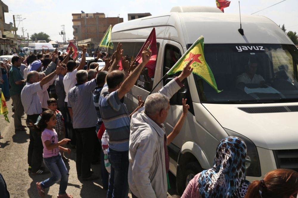 Kurdish people waving flags flash the V-sign and applaud while lining the road, as the convoy carrying the body of U.S. citizen Keith Broomfield, killed in fighting with the militants of the Islamic State group in Kobani, Syria, is driven by through Suruc, on the Turkey-Syria border. (Lefteris Pitarakis/AP)