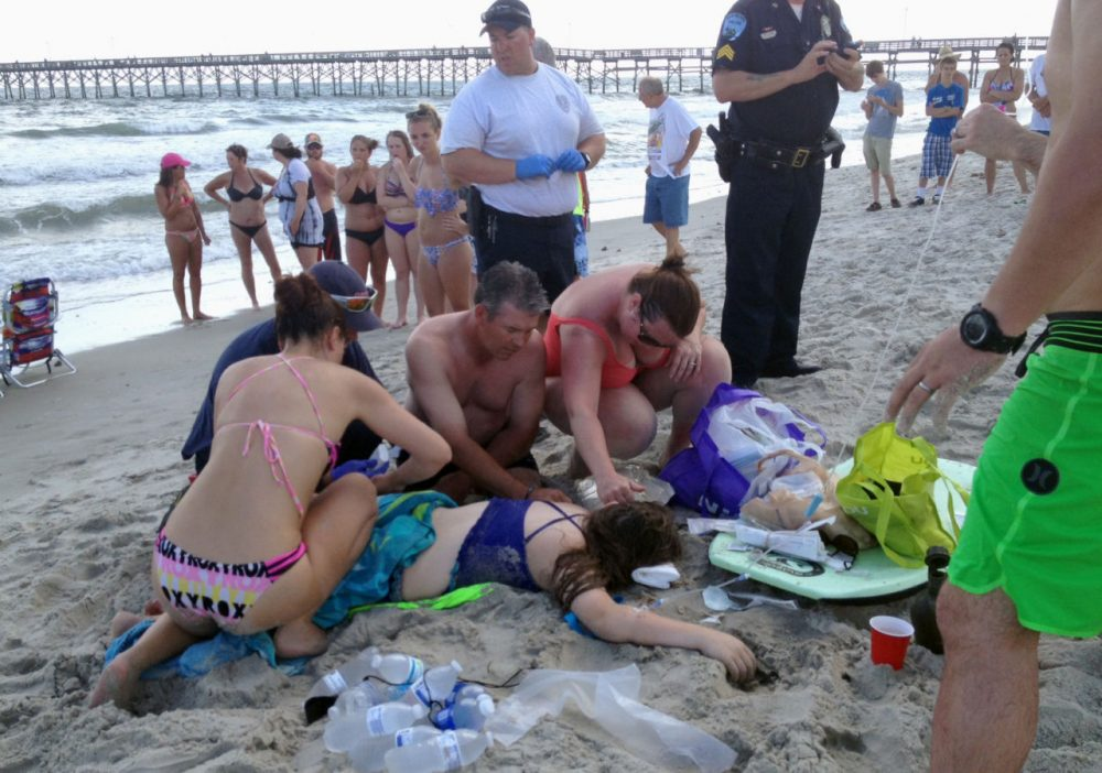 Emergency responders assist a teenage girl at the scene of a shark attack in Oak Island, N.C., Sunday, June 14, 2015. Mayor Betty Wallace of Oak Island, a seaside town bordered to the south by the Atlantic Ocean, said that hours after the girl suffered severe injuries in a shark attack Sunday a teenage boy was also severely injured. (Steve Bouser/The Pilot, Southern Pines, N.C. via AP)