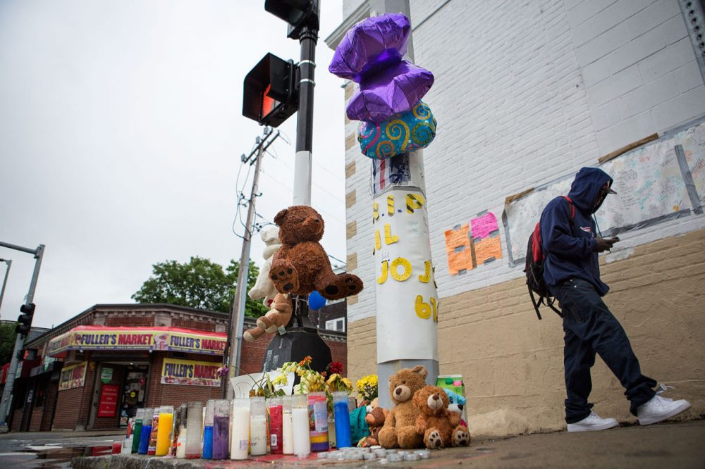 A memorial has popped up for Jonathan Dos Santos on the corner of Washington and Fuller streets in Dorchester, where he was shot and killed last week. (Jesse Costa/WBUR)