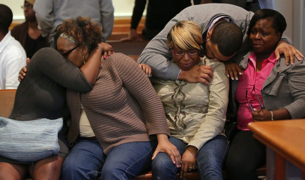 The family and supporters of Dushawn Taylor-Gennis, including his mother Genneane Gennis, seated second from right, react at the end of the session in Dorchester Municipal Court in Boston, Monday. Taylor-Gennis and Raeshawn Moody have been charged with gunning down Jonathan Dos Santos out riding his bike and have been held without bail. (Pat Greenhouse/The Boston Globe via AP, Pool)