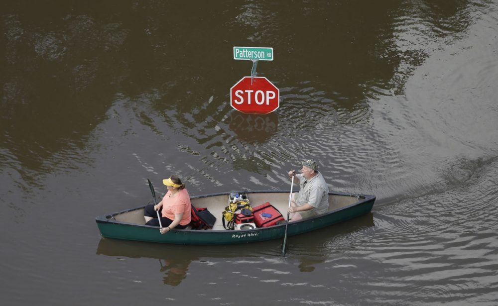 In this aerial photo, people canoe through floodwaters past a stop sign near Bear Creek Park Saturday, May 30, 2015, in Houston. The Colorado River in Wharton and the Brazos and San Jacinto rivers near Houston are the main focus of concern as floodwaters move from North and Central Texas downstream toward the Gulf of Mexico. (David J. Phillip/AP)