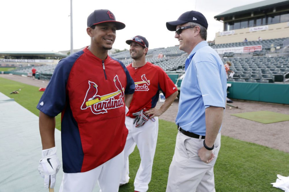 In this Feb. 25, 2013 photo, Houston Astros general manager Jeff Luhnow, right, talks to St. Louis Cardinals center fielder Jon Jay, left, and second baseman Daniel Descalso before an exhibition spring training baseball game in Jupiter, Fla. Major League Baseball says it is cooperating with a federal investigation into an illegal breach of the Astros' internal operations database, amid a report that the Cardinals were responsible for the hack. (Julio Cortez/AP)