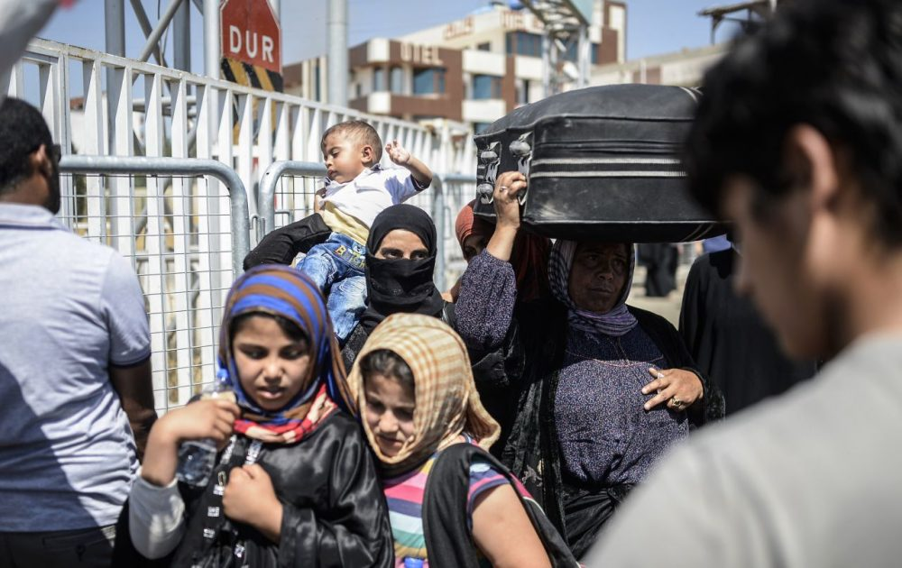 Syrian refugees wait prior to go back to the northern Syrian town of Tal Abyad at the Turkish border post of Akcakale, the province of Sanliurfa, on June 17, 2015. The first Syrian refugees returned to the border town of Tal Abyad from Turkey after it was liberated from the Islamic State group, an AFP journalist reported. Kurdish forces took the strategic town on Tuesday after several days of intense fighting, which sparked an exodus of more than 23,000 refugees into neighbouring Turkey. (Bulent Kilic/AFP/Getty Images)