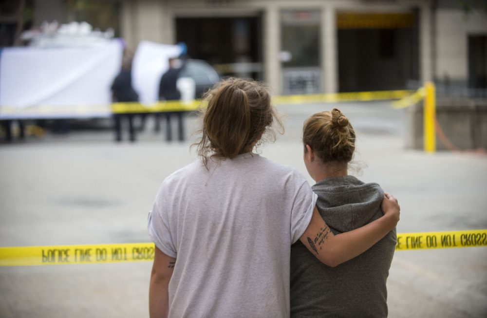 Two women embrace while watching sheriff's deputies move the body of a person who died when a fourth floor balcony collapsed in Berkeley, Calif. on Tuesday, June 16, 2015. (Noah Berger/AP)