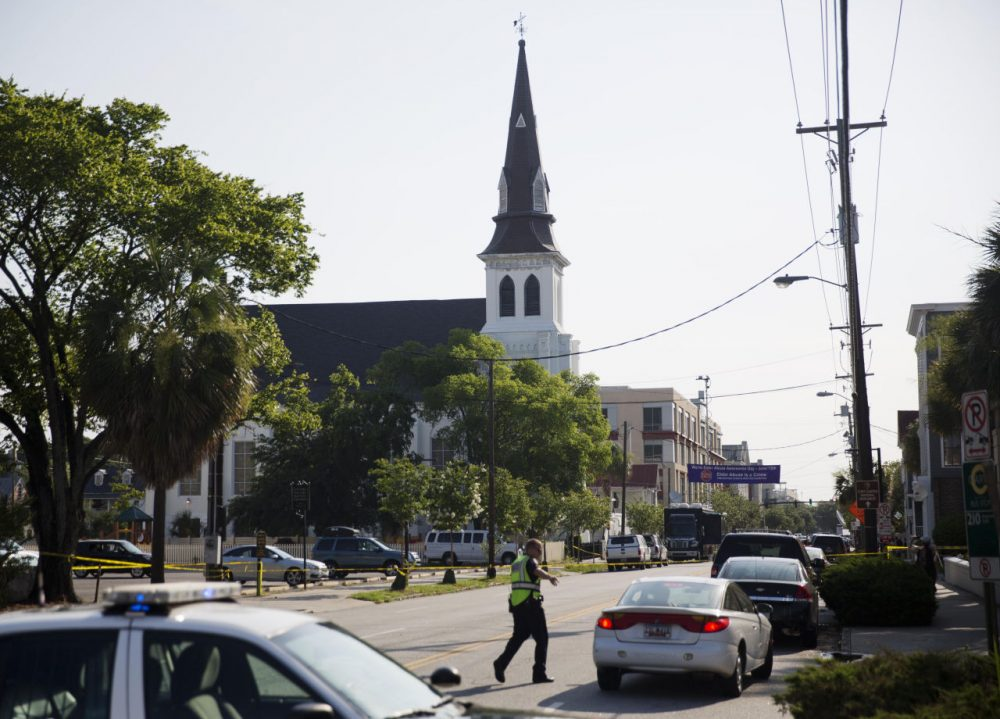 The steeple of Emanuel AME Church rises above the street as a police officer tells a car to move as the area is closed off following Wednesday's shooting, Thursday, June 18, 2015 in Charleston, S.C. (David Goldman/AP)