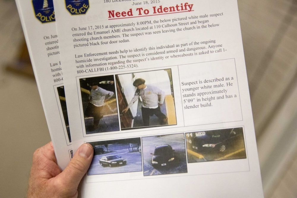 Charleston Emergency Management Director Mark Wilbert holds a flier distributed to media, Thursday, June 18, 2015, with surveillance footage of a suspect wanted in the connection of a shooting Wednesday at Emanuel AME Church during a news conference, in Charleston, S.C. (David Goldman/AP)