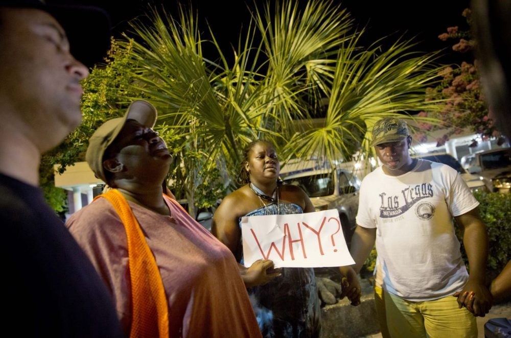Surreace Cox of North Charleston, S.C., holds a sign during a prayer vigil down the street from the Emanuel AME Church early Thursday following a shooting Wednesday night that killed nine people. (David Goldman/AP)
