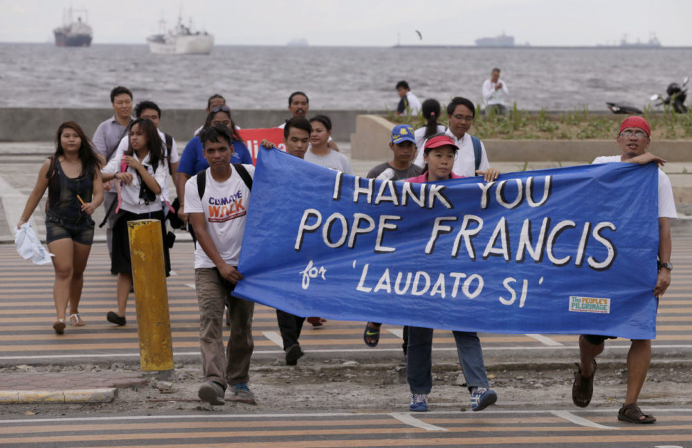 Environmental activists carry a banner as they march towards a Roman Catholic church to coincide with Pope Francis' encyclical on climate change in Manila, Philippines. In a 190-page document released Thursday, Francis describes ongoing human damage to nature. (Bullit Marquez/AP)