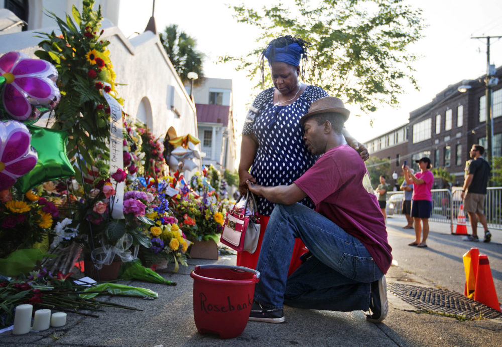 Allen Sanders, right, kneels next to his wife Georgette, both of McClellanville, S.C., as they pray at a sidewalk memorial in memory of the shooting victims in front of Emanuel AME Church Saturday. (David Goldman/AP)