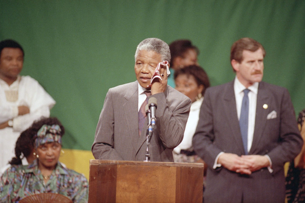 Nelson Mandela wipes his brow in the hot, humid gymnasium of the Madison Park High School in the Roxbury section of Boston 25 years ago. An exhuberant crowd packed the gymnasium for Mandela's appearance. (Jim Gerberich/AP)