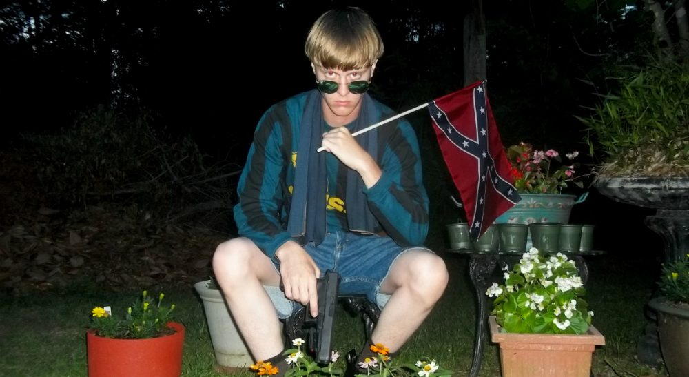 This undated image that appeared on Lastrhodesian.com, a website being investigated by the FBI in connection with Charleston, S.C., shooting suspect Dylann Roof, shows Roof posing for a photo while holding a Confederate flag. (Lastrhodesian.com via AP)