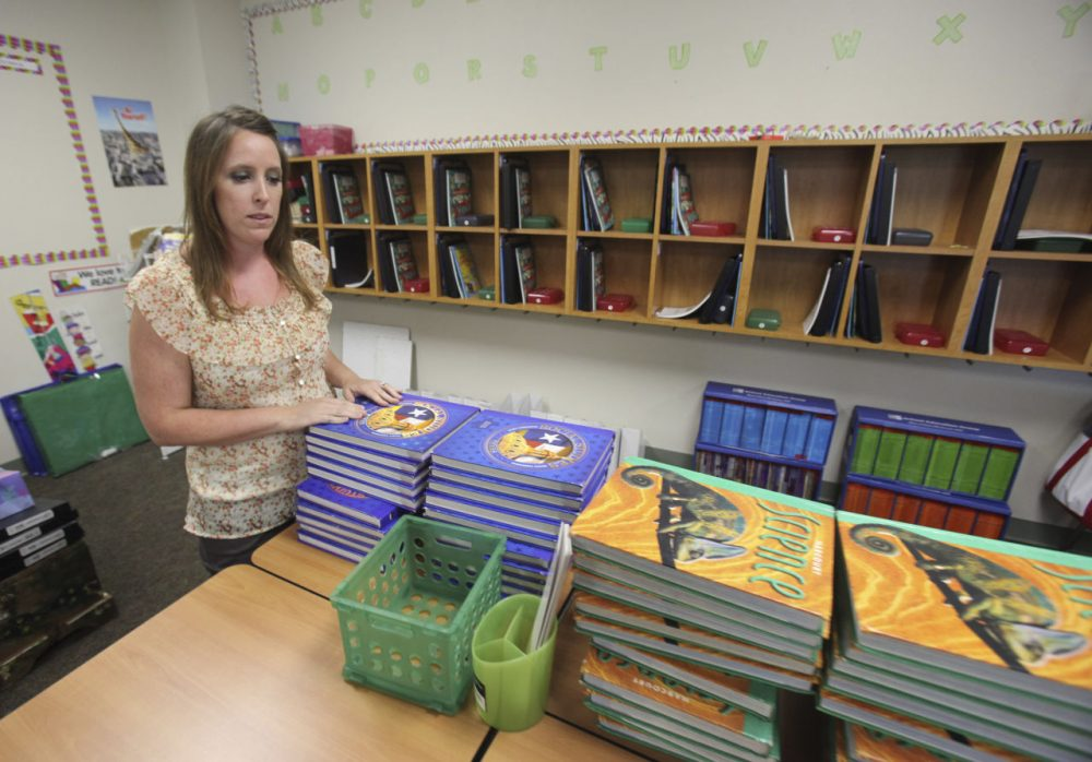 Fourth grade teacher Christy Goff looks over textbooks as she prepares her classroom for the first day of school at Caprock Elementary School in the Keller Independent School District in Fort Worth, Texas, Aug. 17, 2011. (LM Otero/AP)
