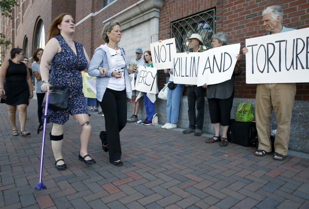 Boston Marathon bombing victim Erika Brannock and her mother Carol Downing walk past demonstrators outside federal court in Boston Wednesday. (Michael Dwyer/AP)