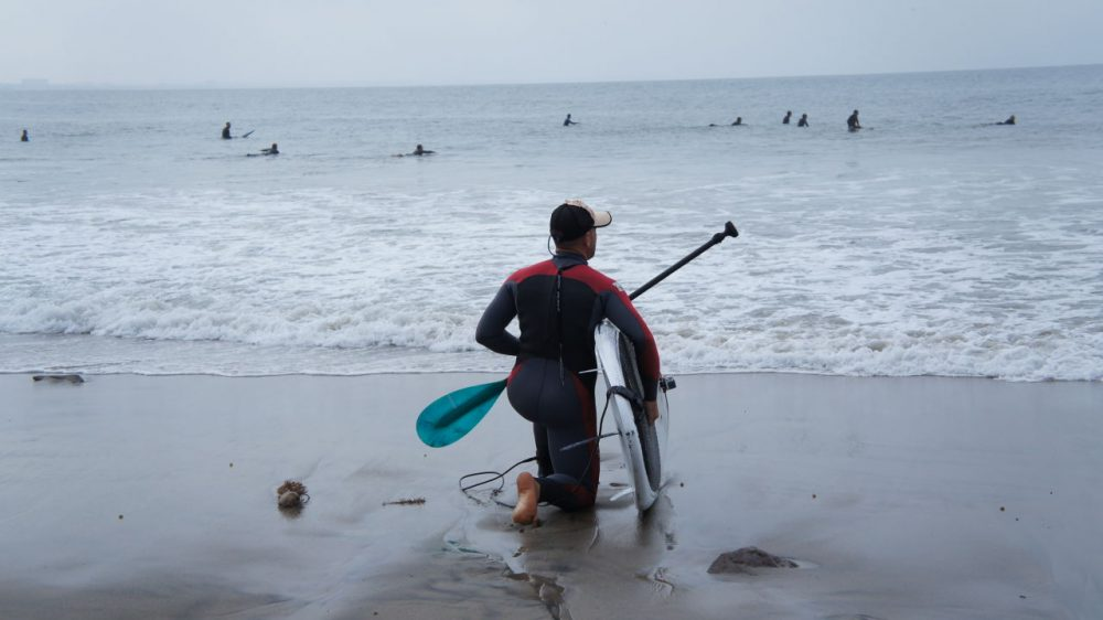 A paddle boarder surveys waves in Malibu before going into the water. (Saul Gonzalez/Only A Game)