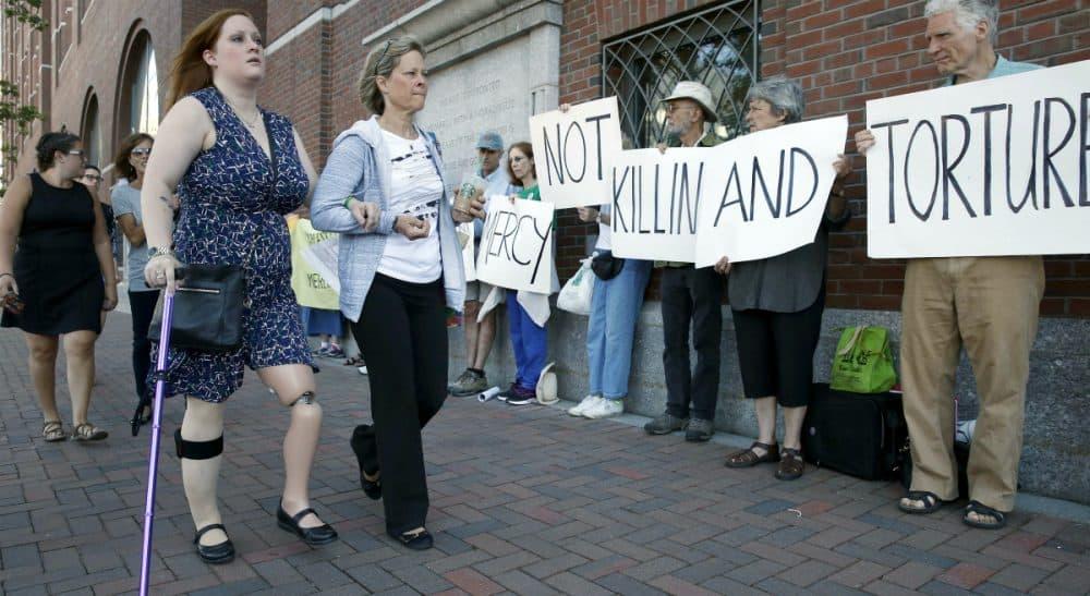 Boston Marathon bombing victim Erika Brannock, left, and her mother Carol Downing, right, walk past demonstrators outside federal court in Boston, Wednesday, June 24, 2015. (Michael Dwyer/AP)