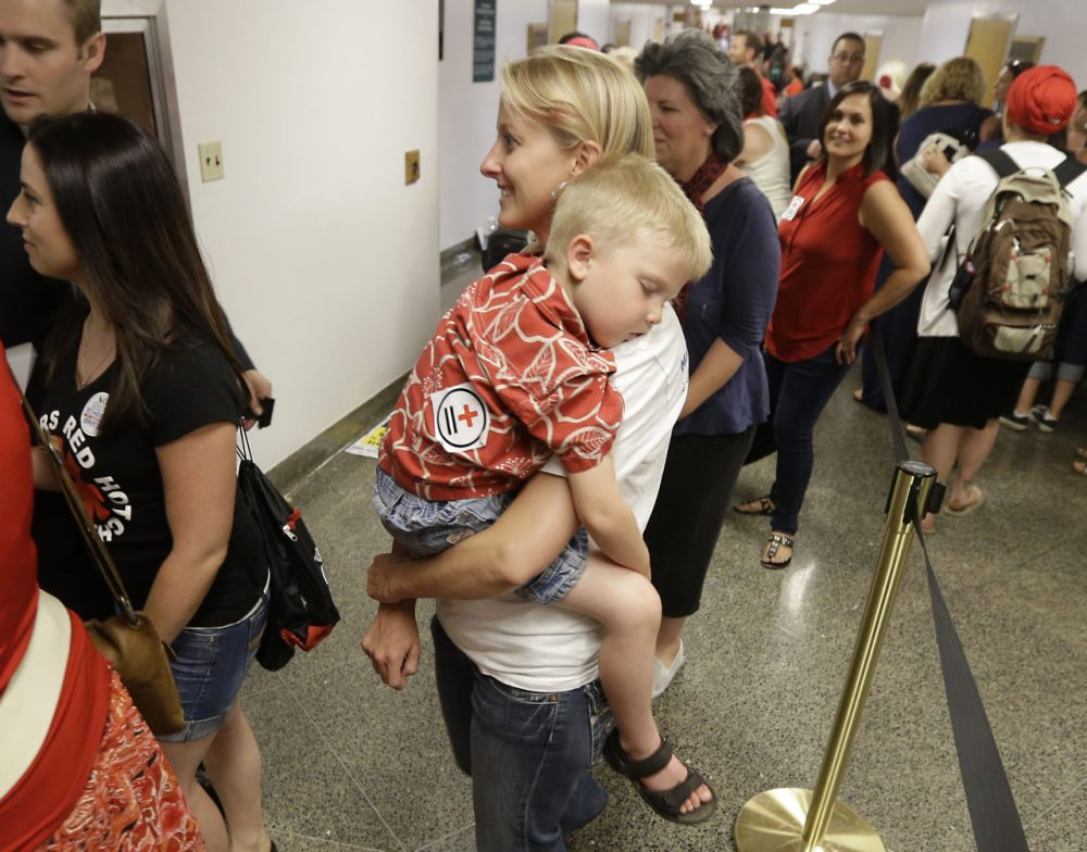 Christy Pritchard carries her son, Zachary, 3, as she waits to appear before the Assembly Health Committee to voice her opposition to a measure mandating that schoolchildren be vaccinated at the Capitol in Sacramento, Calif., Tuesday, June 9, 2015. (Rich Pedroncelli/AP)