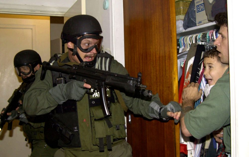 Elian Gonzalez is held in a closet by Donato Dalrymple, one of the two men who rescued the boy from the ocean, right, as government officials search the home of Lazaro Gonzalez for the young boy, early morning, April 22, 2000, in Miami, Florida. Armed federal agents seized Elian Gonzalez from the home of his Miami relatives before dawn, firing tear gas into an angry crowd as they left the scene with the weeping 6-year-old boy. (Alan Diaz/AP)