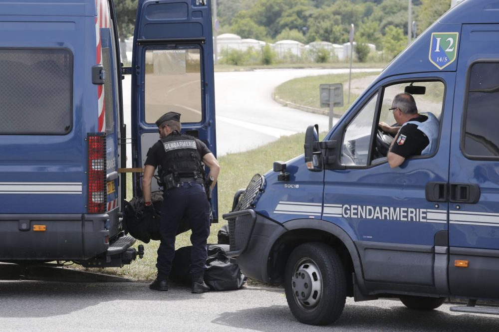 Riot police officers block the area where an attack took place, Friday, June 26, 2015 in Saint-Quentin-Fallavier, southeast of Lyon, France. A man with suspected ties to French Islamic radicals rammed a car Friday into an American gas factory in southeastern France, triggering an explosion that injured two people, officials said. The severed head of a local businessman was left hanging at the factory's entrance, along with banners with Arabic inscriptions, they said. (Laurent Cipriani/AP)