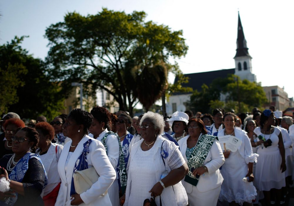 Mother Emanuel African Methodist Episcopal church is seen in the background as women dressed in white wait to enter the funeral service where U.S. President Barack Obama will deliver the eulogy for South Carolina State senator and Rev. Clementa Pinckney who was killed along with eight others in a mass shooting June 26, 2015 in Charleston, South Carolina. (Win McNamee/Getty Images)