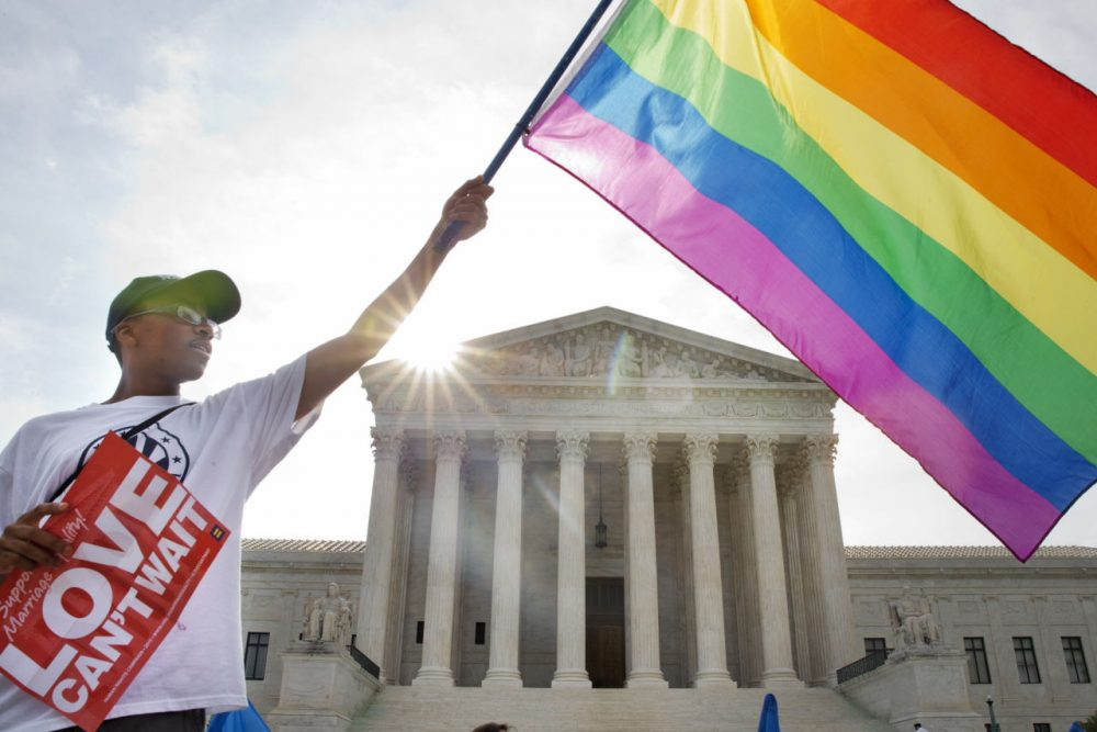 Carlos McKnight of Washington, waves a flag in support of gay marriage outside of the Supreme Court in Washington, Friday June 26, 2015. (Jacquelyn Martin/AP)
