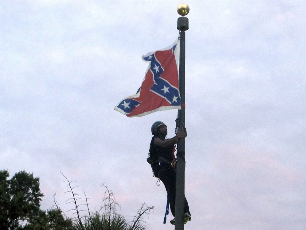 Bree Newsome of Charlotte, N.C., climbs a flagpole to remove the Confederate battle flag at a Confederate monument in front of the Statehouse in Columbia, S.C., on Saturday, June, 27, 2015. She was taken into custody when she came down. The flag was raised again by capitol workers about 45 minutes later. (Bruce Smith/AP)