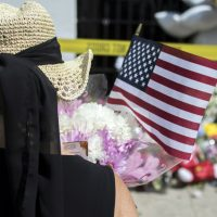 A woman pauses before laying a bouquet of flowers and an American flag at a memorial, Friday, June 19, 2015 in front of the Emanuel AME Church in Charleston, S.C. (Stephen B. Morton/AP)