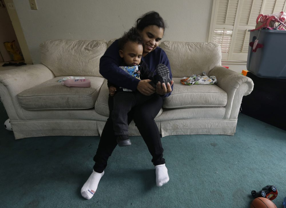 Shannon Henderson, gets her son, Justin, 1, dressed before leaving home for her job as a part-time customer service representative at Wal-Mart in Sacramento, Calif. Henderson is one of an estimated 40 million American workers for who calling in sick is a luxury. If they don't work, they don't get paid. (Rich Pedroncelli/AP)