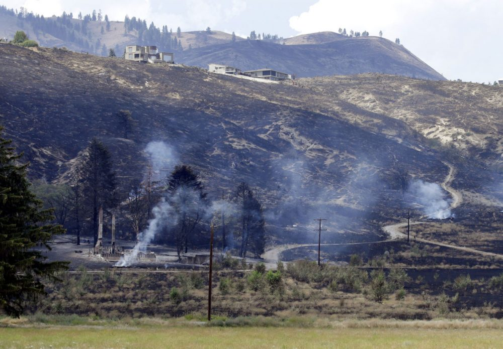 The foundation and chimneys from a destroyed home continue to smolder from a wildfire that raced through the area the night before, Monday, June 29, 2015, in Wenatchee, Wash. (Elaine Thompson/AP)