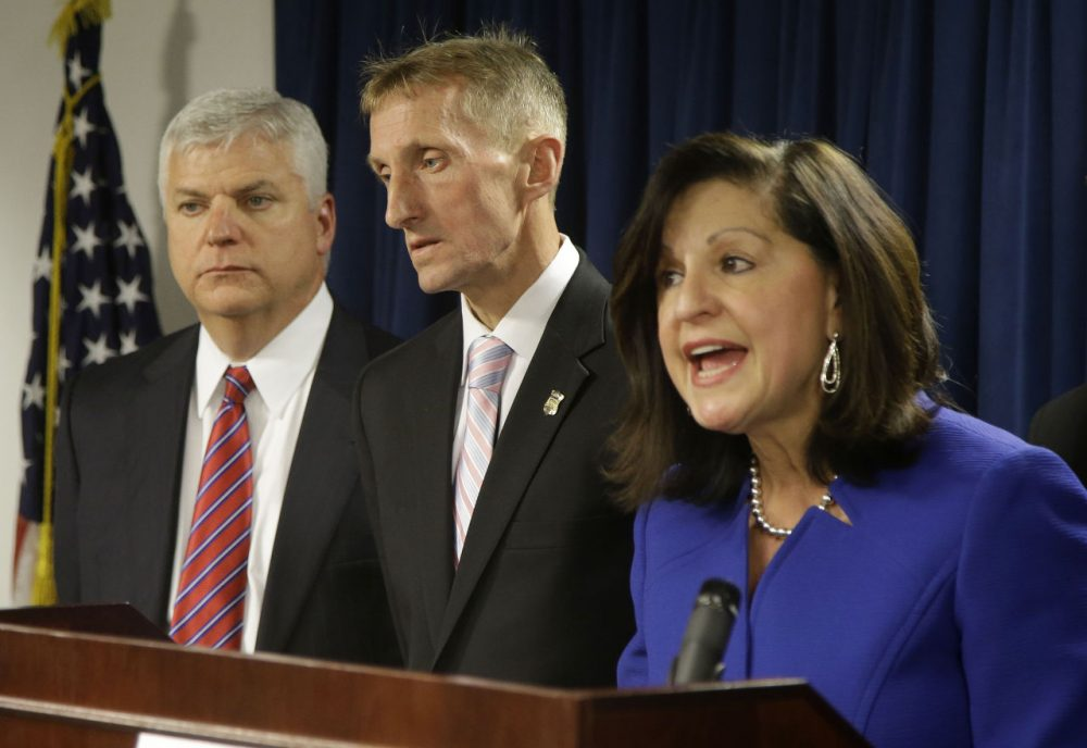 U.S. Attorney Carmen Ortiz, right, speaks alongside Suffolk District Attorney Daniel Conley, left, and Boston Police Commissioner William Evans, during a news conference Thursday in Boston. Federal authorities say 48 members and associates of Boston's most powerful gang have been indicted on drug and gun charges. Seven remain at large. (Stephan Savoia/AP)