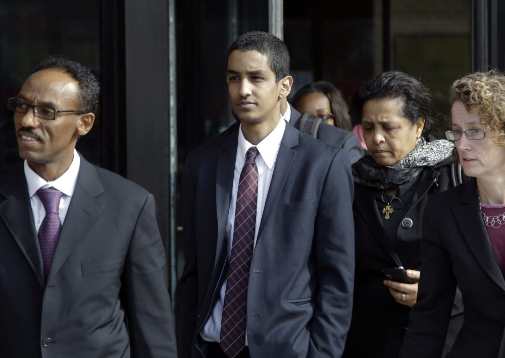 Robel Phillipos, center, departs federal court with his attorney in October 2014. On Friday he was sentenced to three years in prison for lying to law enforcement investigating the Boston Marathon bombing. (Stephan Savoia/AP)