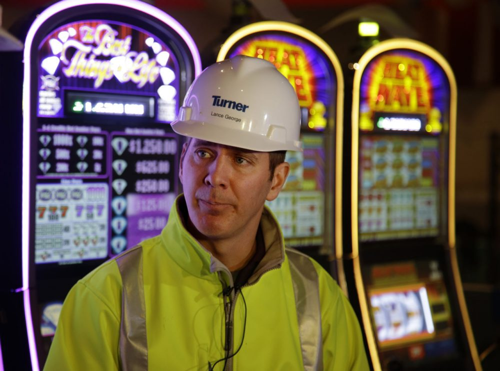 Lance George, Plainridge Park Casino's general manager, stands in front of slot machines on the nearly-completed gambling floor Monday, May 11, 2015, in Plainville, Mass. Penn National Gaming has invested about $250 million to transform the harness racing and simulcast betting facility into a regional destination scheduled to have is grand opening next month. ( (AP Photo/Stephan Savoia)