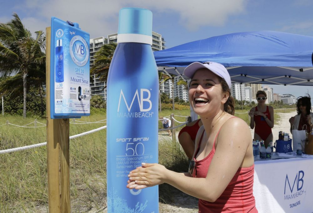 In March, Miami installed several sunscreen dispensers that are similar to those that are coming to Boston this summer. Pictured here, Rachel Gerber, of New York City, uses a sunscreen dispenser in Miami Beach, Florida. (Alan Diaz/AP)