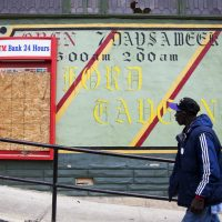 A man walks past the damaged Oxford Tavern in Baltimore, MD, on April 30, 2015. In a presidential campaign where candidates are jockeying to be champions of the middle class and courting donations from the wealthy, the poor are inching their way into the debate. Systemic problems have trapped many of the 45 million Americans living in poverty. But addressing the economic, education and security issues that have plagued underprivileged regions of America for decades remains a politically elusive challenge. (David Goldman/AP)