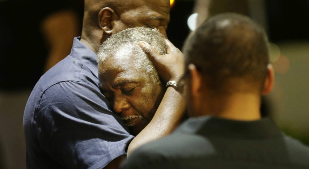 Worshippers embrace following a group prayer across the street from the scene of a shooting at Emanuel AME Church, Wednesday, June 17, 2015, in Charleston, S.C. (David Goldman/AP)