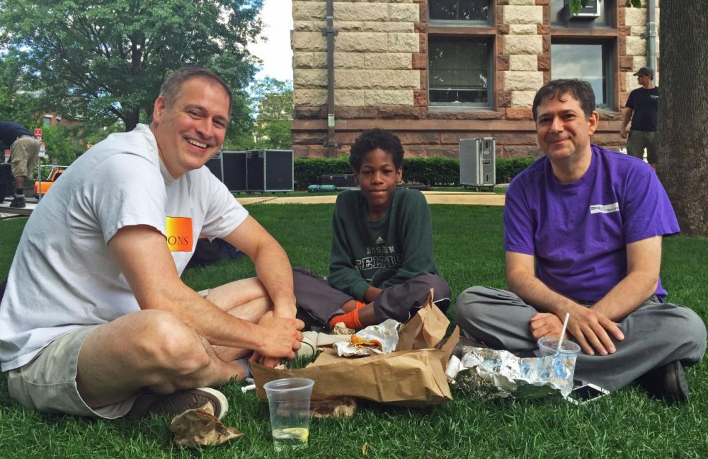 Don Picard and Robert DeBenedictis eat lunch with their son James on the lawn by Cambridge City Hall Friday. It was here back in 2004 that Picard and DeBenedictis were among the first gay couples granted marriage licenses in Massachusetts. (Curt Nickisch/WBUR)