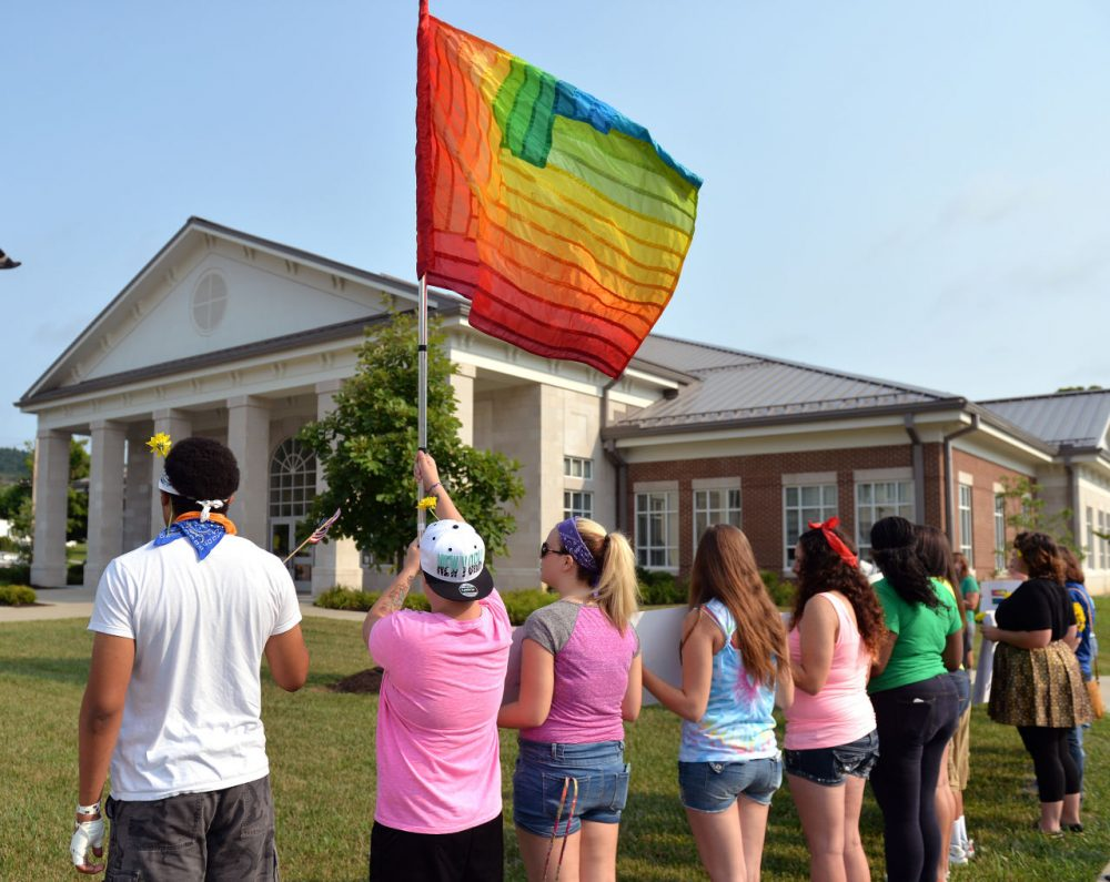 Protesters waive a rainbow flag on the front lawn of the Rowan County Judicial Center, Tuesday, June 30, 2015, in Morehead, Ky. The protest was being held against Rowan County Clerk Kim Davis, who, due to the ruling of the Supreme Court of the United States and her own religious beliefs, has refused to issue any marriage licenses in the county. (Timothy D. Easley/AP)