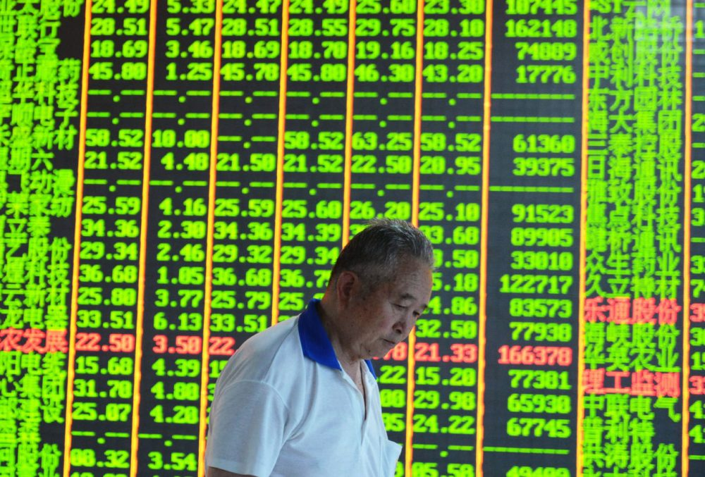 An investor walks past a share prices board at a security firm in Hangzhou, eastern China's Zhejiang province on June 30, 2015.  (STR/AFP/Getty Images)