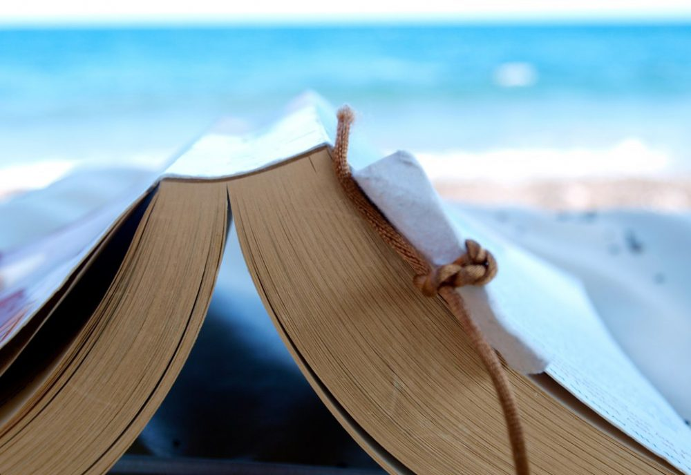 Reading a book at the beach. (simon_cocks/Flickr)