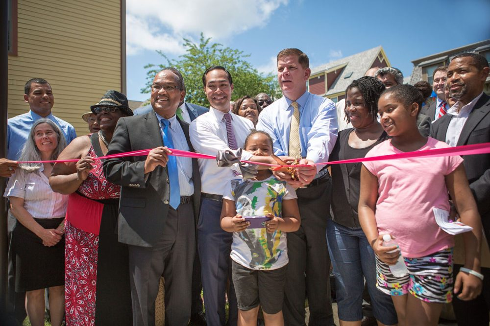 Mayor Marty Walsh,  U.S. Housing Secretary Julián Castro, City Councilor Charles Yancey and members of the community prepare to cut the ribbon during a ceremony at the new Quincy Heights housing development in Dorchester Tuesday. The new development is also home to a 35,000-square-foot shared food production facility. (Jesse Costa/WBUR)